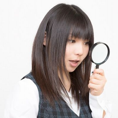 虫眼鏡を覗きこむ女性